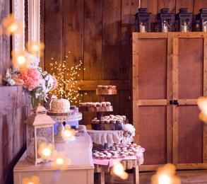 Svatební zákusky na podnose ve stodole